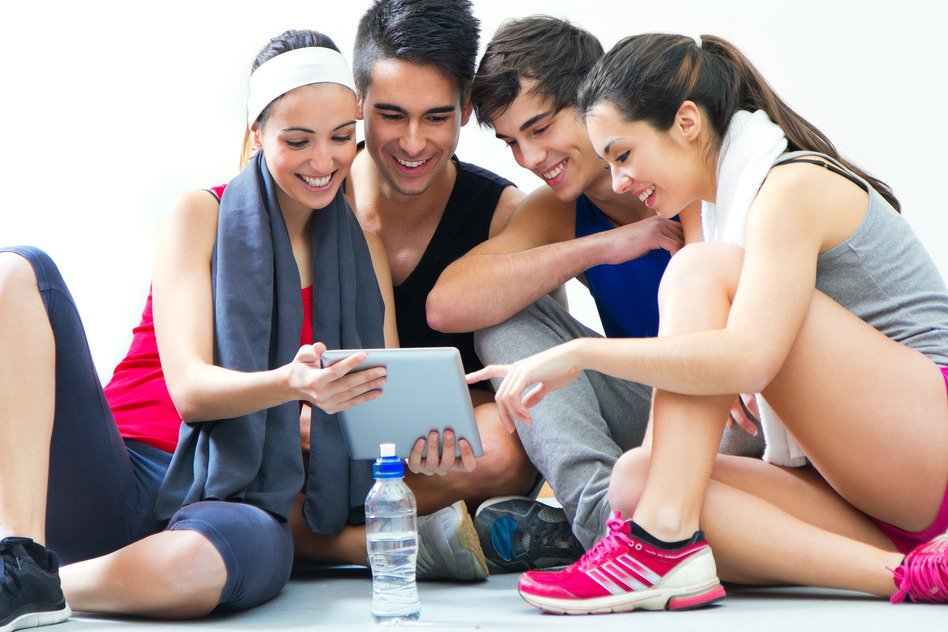 young people looking at digital table in the gym after making ex