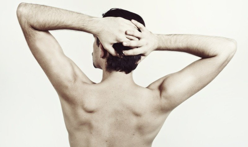 Back of young naked man with beautiful body isolated on white background